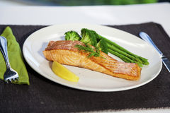 Salmon steak and cookeg vegetables. Salmon steak with vegetables on table setting Stock Photo