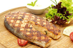Salmon steak. Cooking on the grill with fresh herbs and sauce Royalty Free Stock Photography