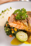 Salmon steak. A salmon steak dish served with mashed potato, sauté spinach and yellow sauce Stock Photography
