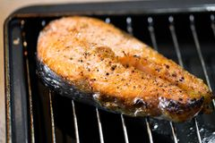 Salmon steak on a frying pan Stock Photo