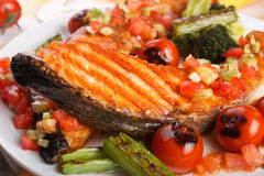 Salmon steak with garnish. (close-up royalty free stock photography