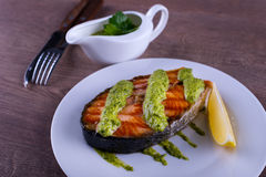 Salmon steak grilled with sauce chimichurri and lemon Royalty Free Stock Image