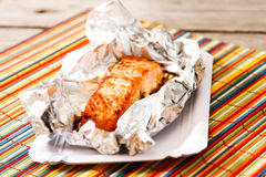 Salmon Steak grilled, wrapped in foils that. On the wooden background with lettuce Stock Images