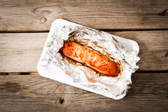 Salmon Steak grilled, wrapped in foils that. On the wooden background with lettuce Stock Photos