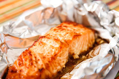 Salmon Steak grilled, wrapped in foils that. On the wooden background with lettuce Royalty Free Stock Image