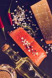 Salmon steak with herbs on black background. In the style of ins Royalty Free Stock Image
