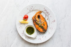 Salmon steak with herbs, lemon, tomato and salsa sauce on a plate. top view. Salmon steak with herbs, lemon, tomato and salsa sauce on a plate. top view Royalty Free Stock Image