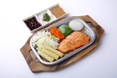 Salmon steak on hot plate with three sauce isolated on white Stock Image
