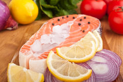 Salmon steak with lemon and onion slices on ice Stock Photos