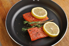 Salmon steak with lemon in a pan Stock Photos
