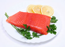 Salmon steak with lemon slices and parsley Stock Photos