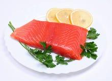 Salmon steak with lemon slices and parsley Stock Photos
