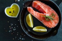 Salmon steak with lemon slices and spices. Dark stone background, top view Royalty Free Stock Photos