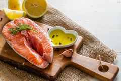 Salmon steak with lemon slices and spices. White wood background Stock Image