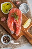 Salmon steak with lemon slices and spices. White wood background, top view Royalty Free Stock Images