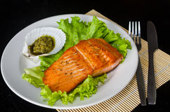 Salmon steak with lettuce and pesto sauce. On white plate royalty free stock photos