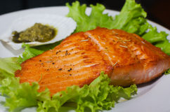 Salmon steak with lettuce and pesto sauce. On white plate royalty free stock photography