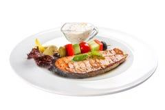 Salmon Steak med gr?nsaker och s?s P? en vit bakgrund fotografering för bildbyråer