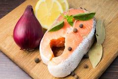 Salmon Steak med kryddor på wood bakgrund Fotografering för Bildbyråer
