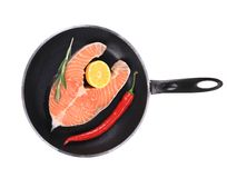 Salmon steak on pan with pepper. Stock Photo