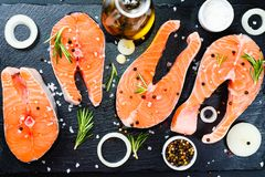 salmon steak, pepper and salt, herbs on black stone concrete table, copy space top view royalty free stock photos