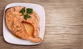 Salmon steak on plate over wooden background Royalty Free Stock Photo