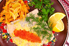 Salmon steak with red caviar. Broiled salmon steak with cream souse and red caviar decorated with dill, lemon and fried onion with carrot royalty free stock image