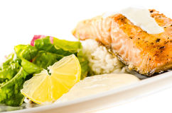 Salmon steak with rice, creamy sauce and side salad Royalty Free Stock Photo