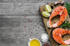 Free Salmon Steak Rich In Omega 3 Oil With Herbs And Spices On Wooden Cutting Board Over Rustic Wooden Background Royalty Free Stock Photography - 115647077
