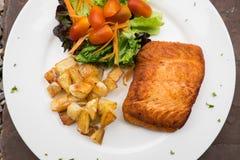 Salmon steak with roast potato and salad Royalty Free Stock Photos
