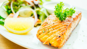 Salmon steak. Salmon meat fillet steak with vegetable salad in white plate Royalty Free Stock Images