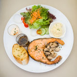 Salmon steak with sauce and salad. On the white dish Royalty Free Stock Image