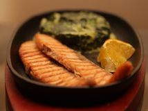 Salmon steak served with spinach Royalty Free Stock Image
