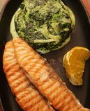 Salmon steak served with spinach Stock Images