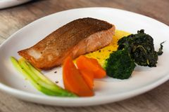 Salmon steak with side dish royalty free stock image