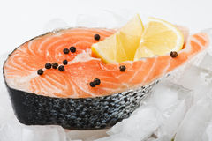 Salmon steak with slices of lemon on the ice. Salmon steak with slices of lemon and black pepper on the ice Stock Photo