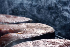 Salmon steak in a smoke and a couple of fried in a pan grill royalty free stock image