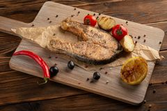 Salmon steak with spices and herbs on wooden background royalty free stock images
