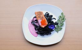 Salmon steak with Squid ink pasta beetroot cream sauce frying fish roe tobiko. Black fresh pasta mixed with creamy pink sauce and orange salty fish roe Stock Photo
