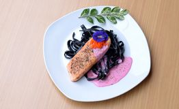 Salmon steak with Squid ink pasta beetroot cream sauce frying fish roe tobiko. Black fresh pasta mixed with creamy pink sauce and orange salty fish roe Stock Images