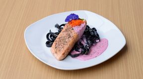 Salmon steak with Squid ink pasta beetroot cream sauce frying fish roe tobiko. stock photography
