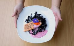 Salmon steak with Squid ink pasta beetroot cream sauce frying fish roe tobiko. Black fresh pasta mixed with creamy pink sauce and orange salty fish roe Stock Photos
