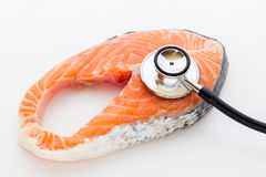 Salmon steak with stethoscope Stock Photos