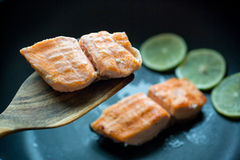 Salmon steak taken up by turner from black pan which has another one and lemon pieces stock photo