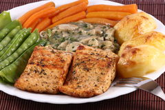 Salmon Steak with Vegetables. Delicious salmon steak with snow peas, baby carrots, baked potatoes and champignon mushrooms with spices in a light sauce Stock Photography