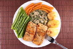 Salmon Steak with Vegetables. Delicious salmon steak with snow peas, baby carrots, baked potatoes and champignon mushrooms with spices in a light sauce Stock Photo