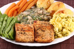 Salmon Steak with Vegetables. Delicious salmon steak with snow peas, baby carrots, baked potatoes, rice and champignon mushrooms with spices in a light sauce Royalty Free Stock Image