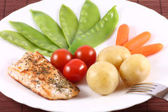 Salmon Steak with Vegetables. Salmon steak with snow peas, baby carrots, baked potatoes and cherry tomatoes Stock Photography