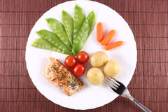 Salmon Steak with Vegetables. Salmon steak with snow peas, baby carrots, baked potatoes and cherry tomatoes Stock Photos