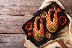 Salmon steak with vegetables on a grill pan. horizontal top view Royalty Free Stock Photography